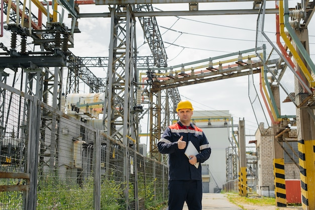 De energie-ingenieur inspecteert de uitrusting van het onderstation. energietechniek. industrie.