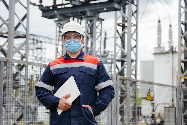 De energie-ingenieur inspecteert de uitrusting van het onderstation
