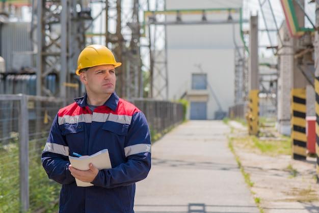 De energie-ingenieur inspecteert de uitrusting van het onderstation.