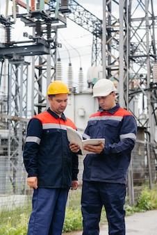 De energie-ingenieurs inspecteren de uitrusting van het onderstation
