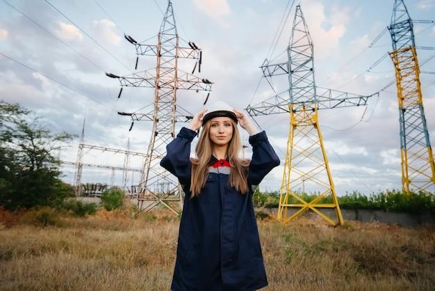 De energiewerker van het meisje draagt een beschermende helm. veiligheid op het werk. energie.