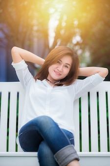 De enige aziatische vrouwenvolvolwassene ontspant zitting bij schommeling in het park geniet van gezond goed het levensconcept