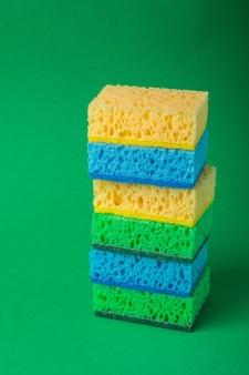 De enige stapel sponsen in blauwe, groene, gele kleuren op groenboekmuur, sluit omhoog