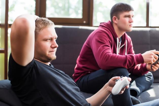 De enthousiaste gamers. twee jonge gelukkig mannen spelen van videogames zittend op de bank