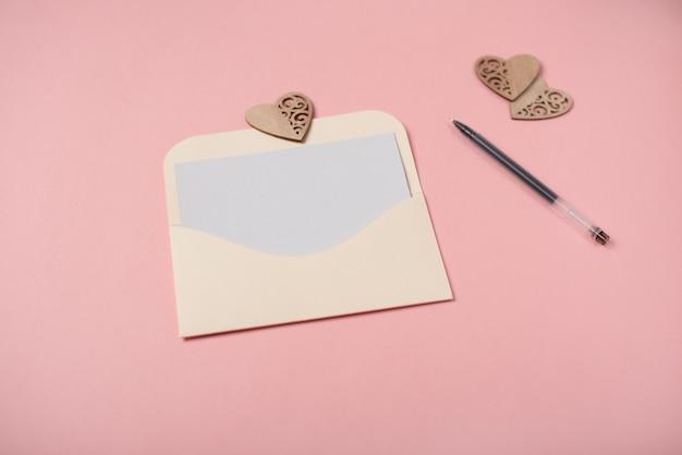 De envelop met een blanco vel papier met houten hartjes op de roze achtergrond. valentijnsdag concept. ruimte voor tekst.