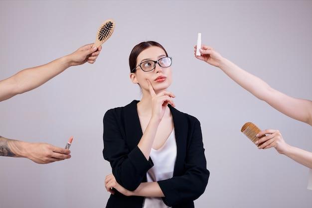 De ernstige bedrijfsvrouw bevindt zich op grijs in een jasje, een t-shirt en een bril. haar armen gekruist. de verkeerde handen geven haar twee kammen en 2 lippenstiften. lady kijkt opzij.