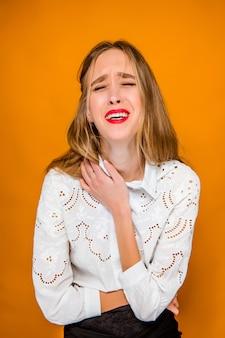 De ernstige gefrustreerd jonge mooie zakenvrouw op oranje muur