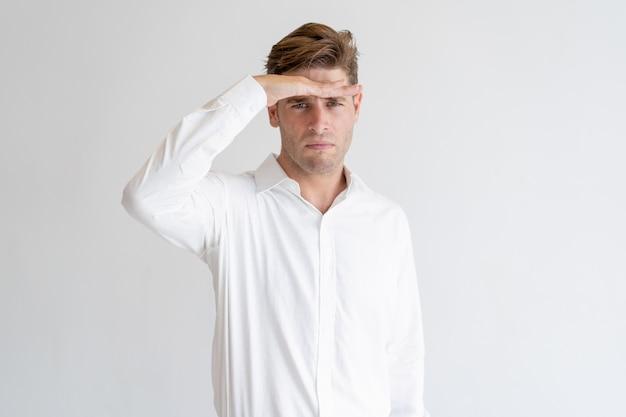 De ernstige hand van de kerelholding bij voorhoofd en het onderzoeken van afstand