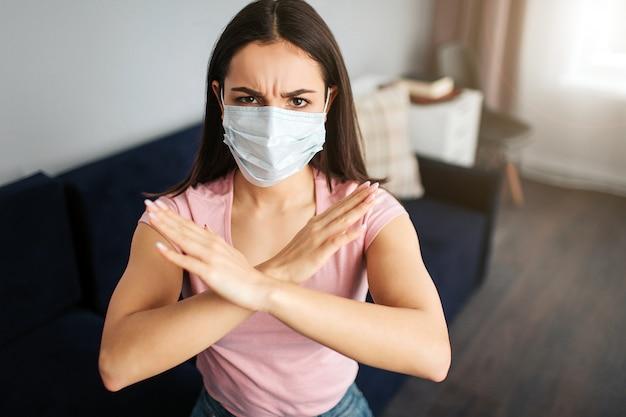 De ernstige jonge vrouw zit op bank. ze bedekte mond met masker. modellen zijn ziek. ze toont stopbord met handen. jonge vrouw boos.