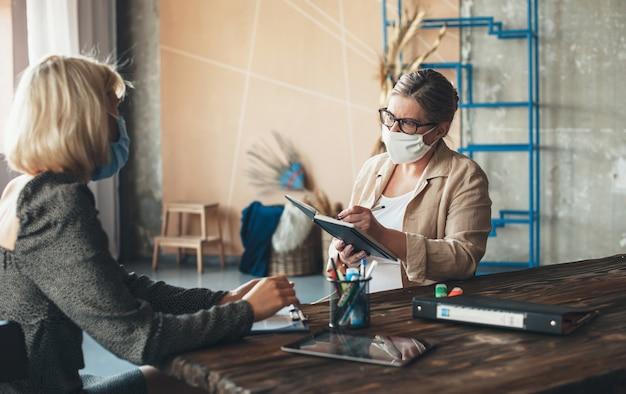 De ernstige kaukasische hogere vrouw met medisch masker op gezicht en glazen bespreekt met een cliënt thuis terwijl iets in het boek schrijft