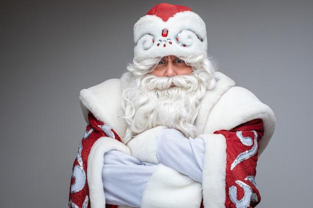 De ernstige kerstman sloeg zijn armen over zijn borst en ontevreden, studioportret op grijs