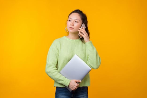 De ernstige vrouw spreekt op de telefoon terwijl haar laptop