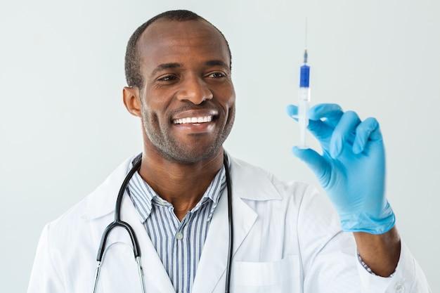 De ervaren dokter van smilign houdt een injectiespuit vast terwijl hij een prik maakt