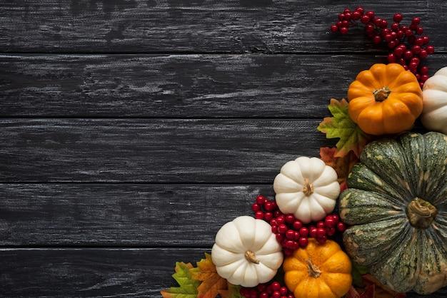 De esdoornbladeren van de herfst met pompoen en rode bessen op houten achtergrond. thanksgiving concep