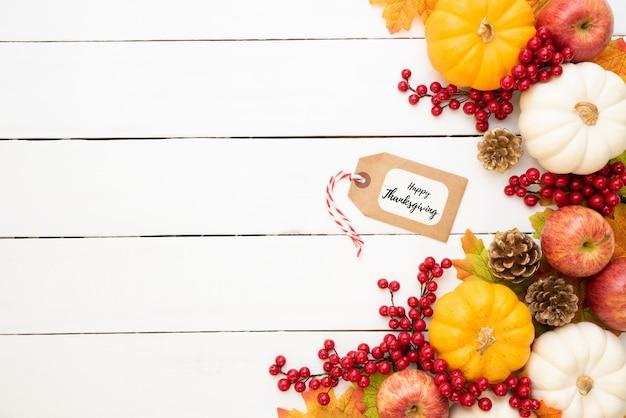 De esdoornbladeren van de herfst met pompoen en rode bessen op houten achtergrond.