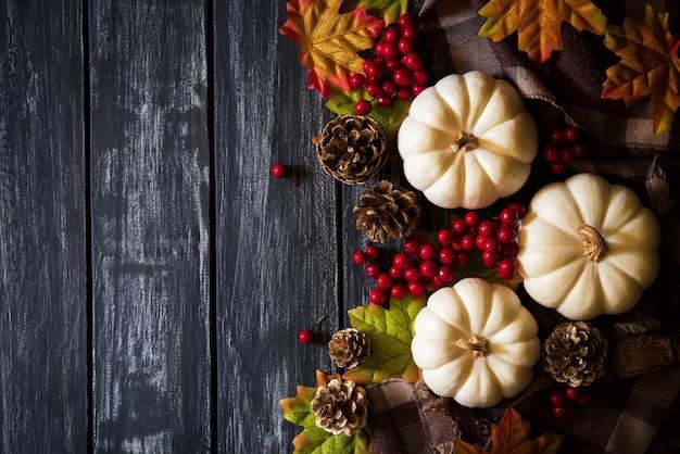 De esdoornbladeren van de herfst met pompoen en rode bessen op oude houten achtergrond. thanksgiving co
