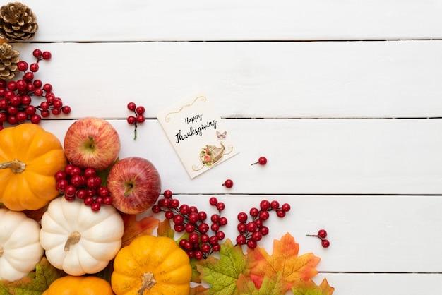 De esdoornbladeren van de herfst met pompoen en rode bessen op witte houten. thanksgiving day concept