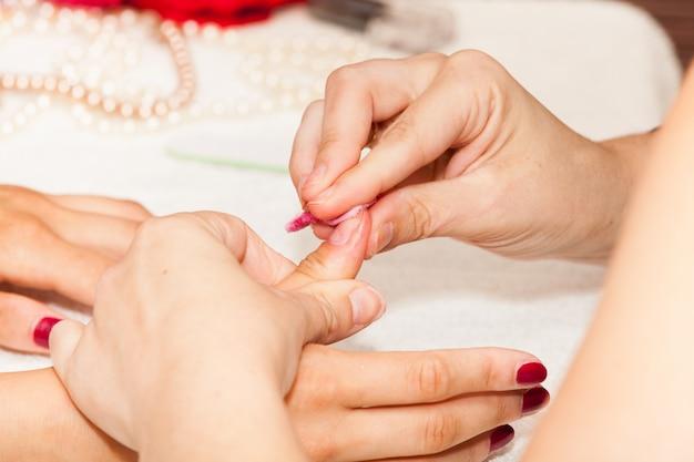De estheticus verwijdert de oude nagellak met een wattenstaafje en remover