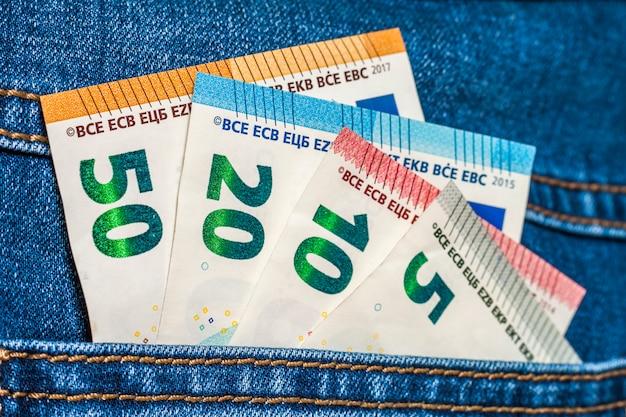 De euro geldbankbiljetten in een zak jeans sluiten omhoog