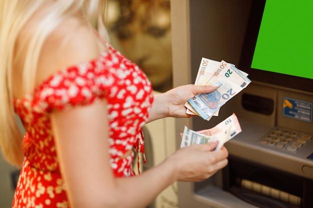 De eurobankbiljetten en atm-machine sluiten omhoog. vrouw die euro geld van contant geldmachine in openlucht neemt. vrouwelijke hand met eurobankbiljetten