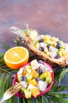 De exotische fruitsalade diende in de helft van een draakfruit en een ananas met palmblad op steenachtergrond, exemplaarruimte. bovenaanzicht