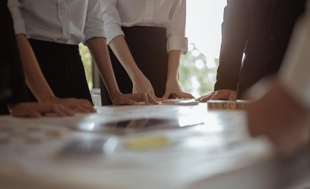 De experts die zich in de vergaderruimte verzamelden, voerden statistische analyses uit op het onderzoeken van financiële cirkeldiagrammen en het plotten van verkopen in groepsbijeenkomsten. verkoopsamenvattingsvergadering, vergadering en bedrijfsconcepten.