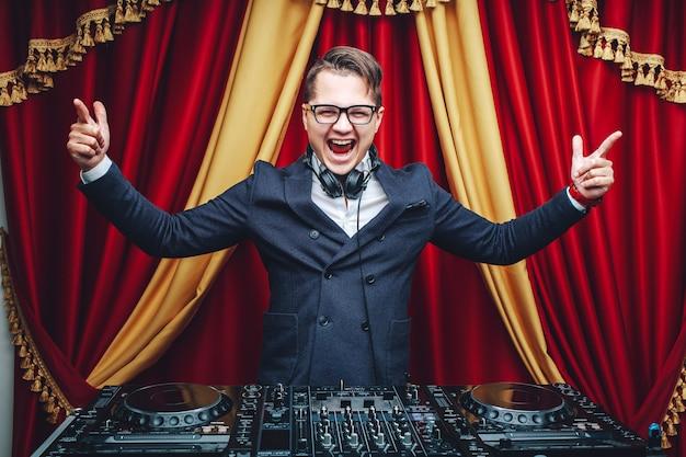 De expressieve modieuze dj in blauwe reeks op het werk heft omhoog zijn handen op een rode achtergrond op