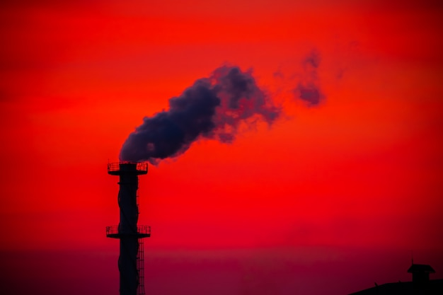 De fabriek gaf rookschoorsteen in zonsondergang vrij. opwarming van de aarde