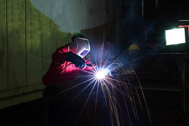 De fabrieksarbeider bij de autofabriek lassen assemblageautomaatdeel