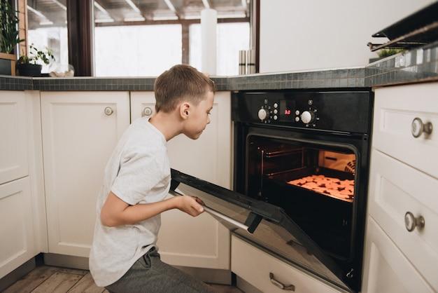 De familie bereidt peperkoekkoekjes in de keuken. vader, moeder, zoon, dochter, broer en zus. kneed deeg, koekjessnijders, nieuwjaar, kerstmis, vakantiediner. grijze homewear.