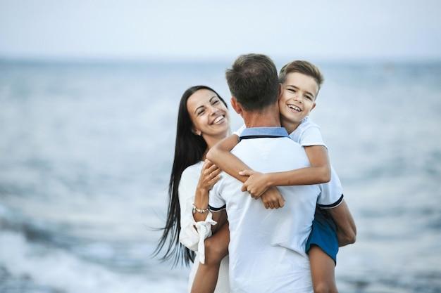 De familie bevindt zich op de kust en glimlacht gelukkig, familieconcept