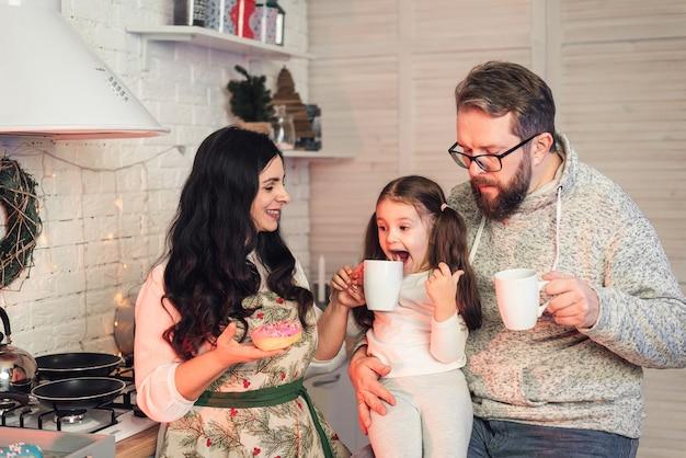 De familie drinkt thee en eet donuts