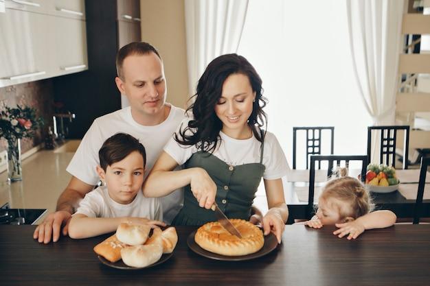 De familie eet taarten. diner bij de bakker. feest in de keuken. het slachten van het voedsel. een vrouw snijdt een taart met een mes