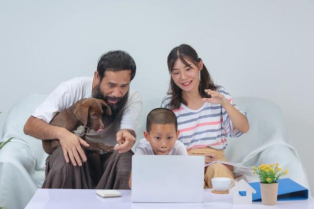 De familie gebruikt thuis samen ontspannen tijd op bank.