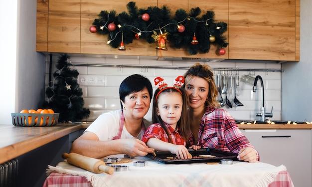 De familie in de keuken bereidt zich voor op kerstmis en heeft plezier met het bakken van koekjes.