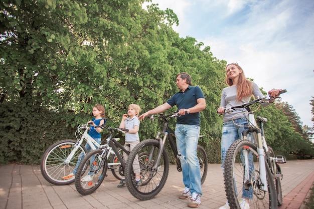 De familie in het park op de fiets