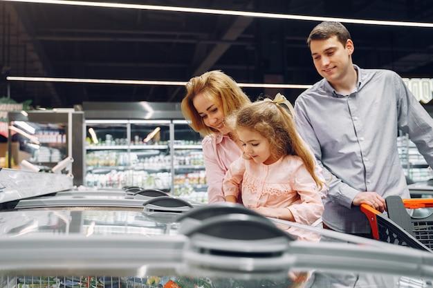 De familie koopt boodschappen in de supermarkt