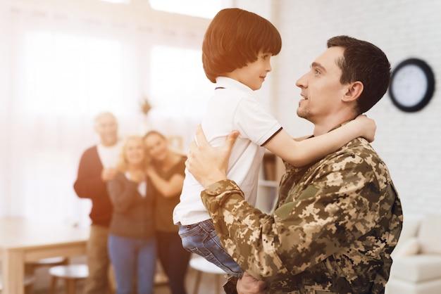 De familie ontmoet thuis een man in camouflage.