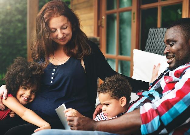 De familie ontspant geluk gebruikend tabletconcept