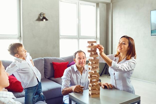 De familie speelt vrolijk gezelschapsspelen terwijl ze aan de tafel in de kamer zitten.