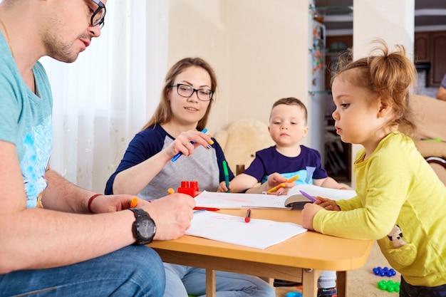 De familie tekent potloden aan een tafel in de kamer