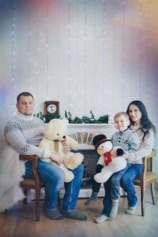 De familie viert samen kerstmis ouders met een kind tussen de feestelijke binnenhaard