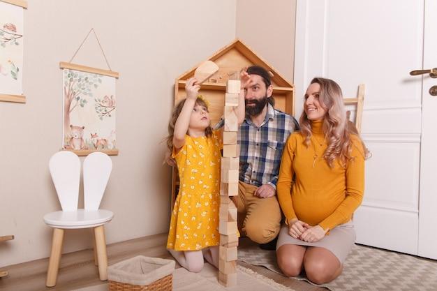 De familie wacht op een nieuwe aanwinst. een zwangere vrouw, haar man en dochter spelen samen in de kinderkamer.