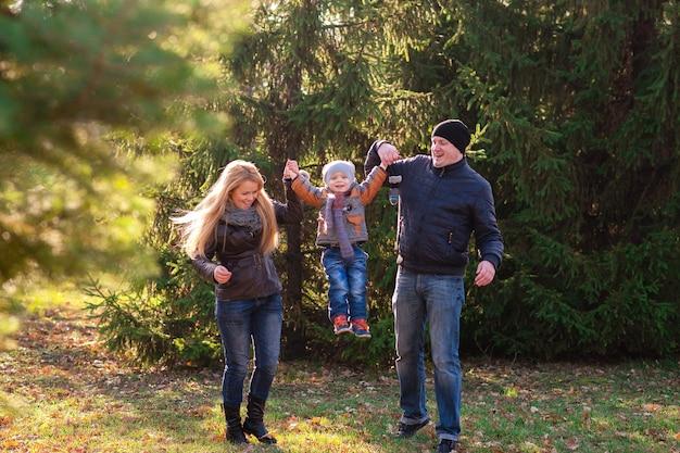 De familie wandelt in het park in de herfst