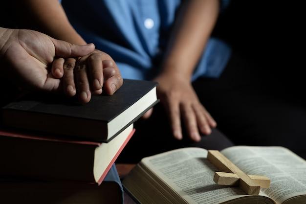 De familiegroep bidt samen op houten lijst