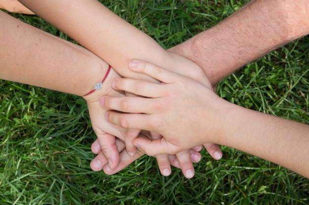 De familiehanden bedekken elkaar met grasachtergrond