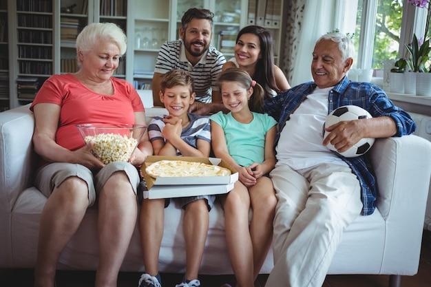De familiezitting van meerdere generaties met popcorn en pizza terwijl het bekijken van voetbalwedstrijd