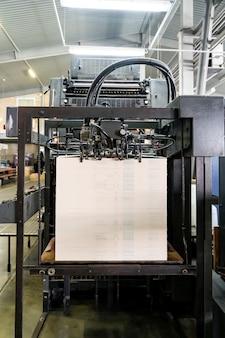 De feeder van de offsetdrukmachine brengt metallic papier door de invoertafel naar de fabriek van de drukeenheid