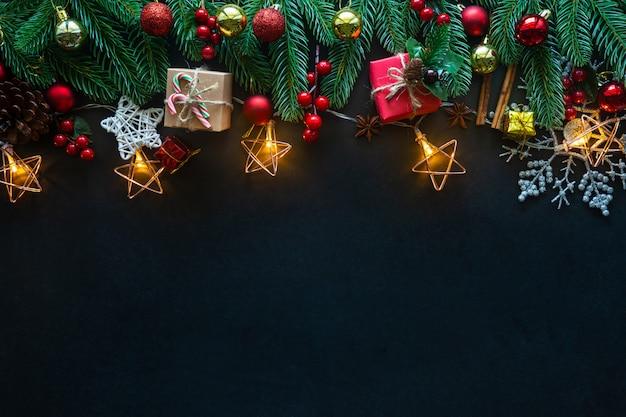 De feestelijke decoratie van vakantiekerstmis op een zwarte achtergrond van vlakte lag.