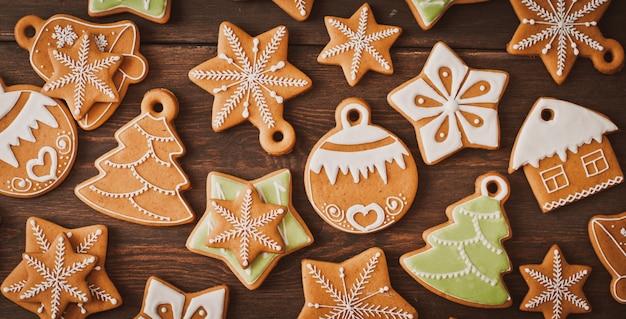 De feestelijke koekjes van de kerstmispeperkoek in de vorm van een ster liggen op een houten donkere bruine achtergrond.